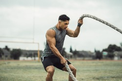 Strong man exercising with battle ropes. Athlete doing battle rope workout outdoors on a field.
