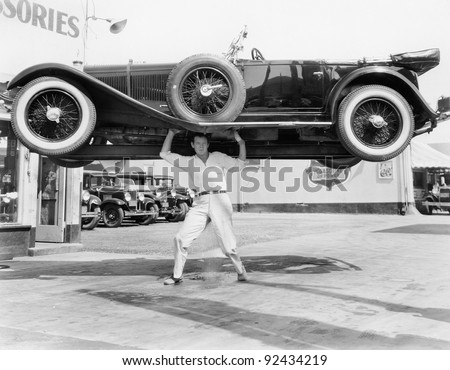 strong man lifting a car over...