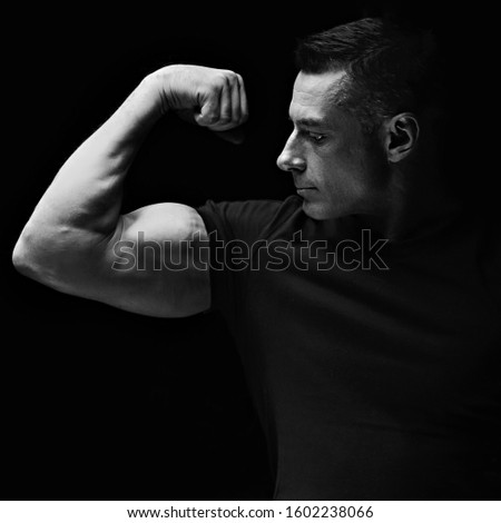 Strong man looking and showing her biceps arm on dark black background. Closeup. Black and white