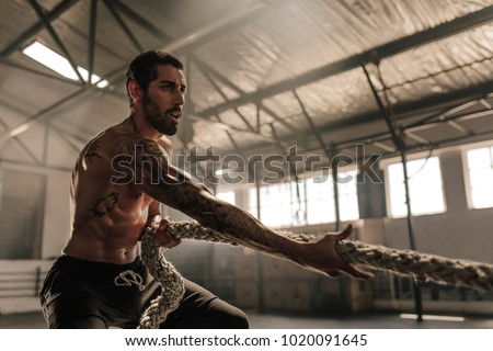 Strong man pulling heavy rope at cross training gym. Male athlete doing exercises with rope at gym.