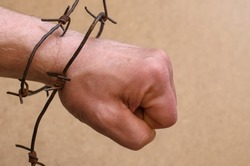 Strong man's hand clenched into a fist and tied with rusty barbed wire,