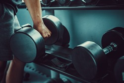 strong man's hand takes a heavy dumbbell in gym