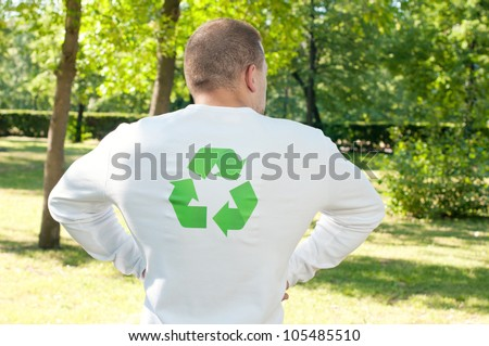 Strong man standing with his back to the camera and flexing his recycling muscles
