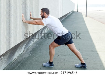 Strong Man Stretching Calf and Leaning on Wall