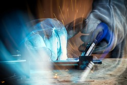Strong man welder in work clothes hard working and welds with a welding machine metal  in the workshop