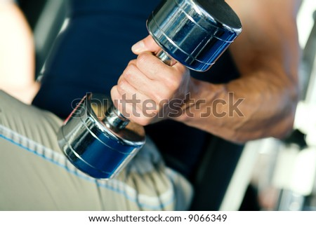 Strong man with dumbbells; focus on hand and dumbbell