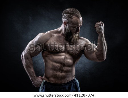 Strong man with perfect abs, shoulders, biceps, triceps and chest. Bodybuilder topless over grunge background.