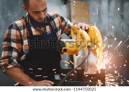 Strong mechanic working on electrical angular grinding machine at metalworking factory, sparks fly apart. Work in process on plant. Horizontal. Flare effect