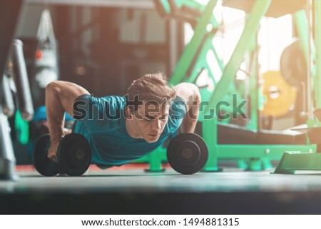 Strong mind, strong body. Young man in sportswear exercising indoors. Copy space on the right side