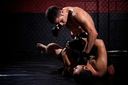 Strong MMA fighter holding his rival down and throwing punches at him during a fight. With plenty of copy space