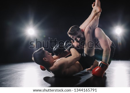 strong mma fighter in boxing gloves doing painful chokehold with legs to another sportsman on floor