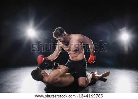 strong mma fighter in boxing gloves punching opponent while sportsman lying on floor