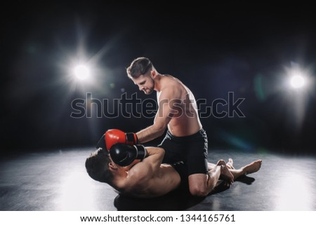 strong mma fighter in boxing gloves sitting on opponent and punching him in head while sportsman lying on floor