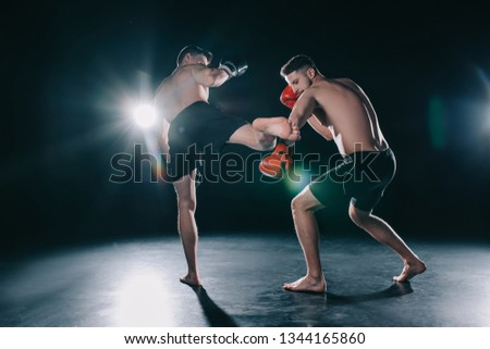 strong mma fighter kicking another sportsman with leg in arm