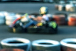 Strong motion blur karting. The picture is out of focus. Racers on races on special safe high-speed tracks limited by car tires. Attraction High-speed ride in carts. Sport karting entertainment