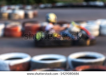 Strong motion blur karting. The picture is out of focus. Racers on races on special safe high-speed tracks limited by car tires. Attraction High-speed ride in carts. Sport karting entertainment #1429080686