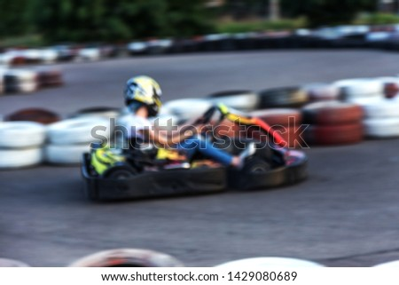Strong motion blur karting. The picture is out of focus. Racers on races on special safe high-speed tracks limited by car tires. Attraction High-speed ride in carts. Sport karting entertainment #1429080689