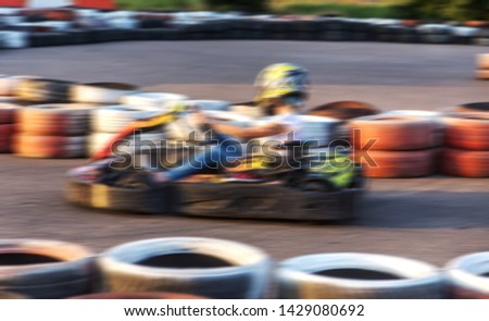 Strong motion blur karting. The picture is out of focus. Racers on races on special safe high-speed tracks limited by car tires. Attraction High-speed ride in carts. Sport karting entertainment #1429080692
