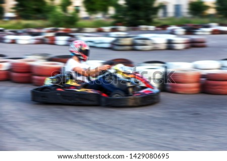 Strong motion blur karting. The picture is out of focus. Racers on races on special safe high-speed tracks limited by car tires. Attraction High-speed ride in carts. Sport karting entertainment #1429080695