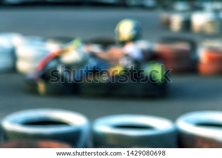 Strong motion blur karting. The picture is out of focus. Racers on races on special safe high-speed tracks limited by car tires. Attraction High-speed ride in carts. Sport karting entertainment #1429080698