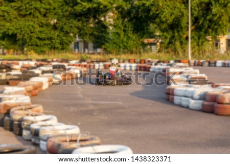 Strong motion blur karting. The picture is out of focus. Racers on races on special safe high-speed tracks limited by car tires. Attraction High-speed ride in carts. Sport karting entertainment #1438323371