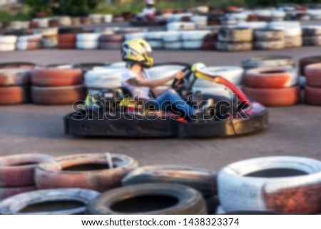 Strong motion blur karting. The picture is out of focus. Racers on races on special safe high-speed tracks limited by car tires. Attraction High-speed ride in carts. Sport karting entertainment #1438323374