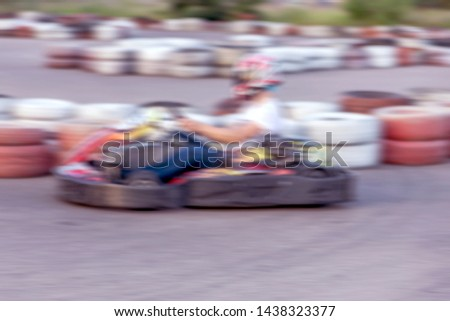 Strong motion blur karting. The picture is out of focus. Racers on races on special safe high-speed tracks limited by car tires. Attraction High-speed ride in carts. Sport karting entertainment #1438323377