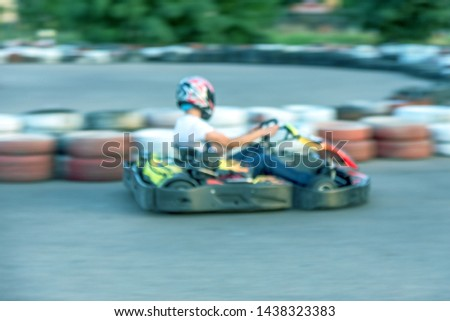 Strong motion blur karting. The picture is out of focus. Racers on races on special safe high-speed tracks limited by car tires. Attraction High-speed ride in carts. Sport karting entertainment #1438323383