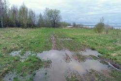 Strong mud on a rural road. Water on the field and country road.Rural landscape with empty countryside dirt wet road. The harsh landscape nature and road through the fields with puddles and mud