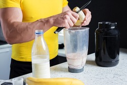 Strong muscle sporty looking man bodybuilder in yellow t-shirt with sharpe knife in hand cutting banana for healthy protein milkshake next to white kitchen counter with black jar and bottle of milk