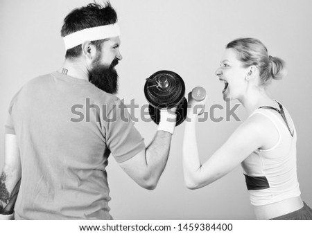 Strong muscles and power. Sport dumbbell equipment. Sporty couple training in gym. Athletic competition. Weight lifting. Happy woman and man workout with barbell. Championships are won at practice. #1459384400