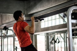Strong muscular athletic Asian man perform bodybuilding by pulling up or chin ups on horizontal bar at sport gym. Hands, arms, shoulder workout. Bodybuilding and healthy lifestyle concept.