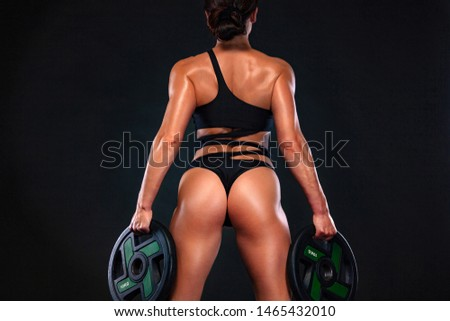 Strong muscular bodybuilder athletic woman pumping up muscles with barbell on black background. Workout bodybuilding concept.