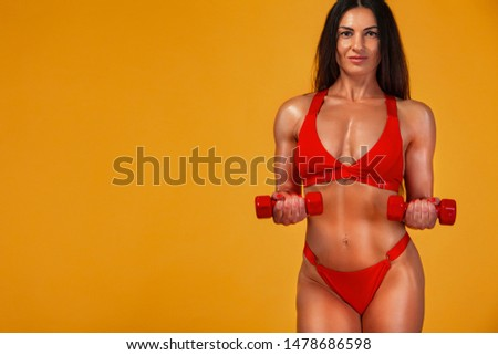 Strong muscular bodybuilder athletic woman pumping up muscles with dumbbells on yellow background. Individual sports recreation. #1478686598