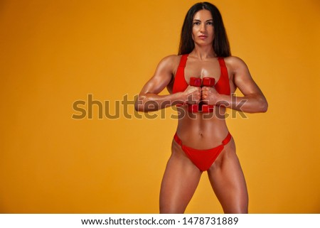 Strong muscular bodybuilder athletic woman pumping up muscles with dumbbells on yellow background. Individual sports recreation. #1478731889