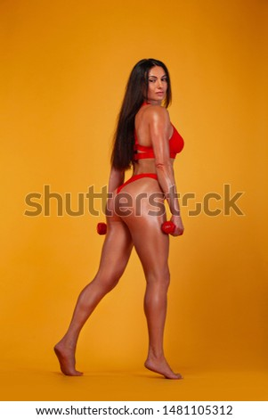 Strong muscular bodybuilder athletic woman pumping up muscles with dumbbells on yellow background. Individual sports recreation. #1481105312