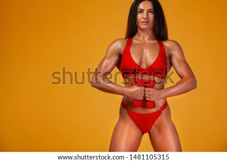 Strong muscular bodybuilder athletic woman pumping up muscles with dumbbells on yellow background. Individual sports recreation. #1481105315