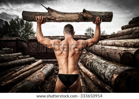 Strong muscular man holding heavy wood trunks Stock photo ©