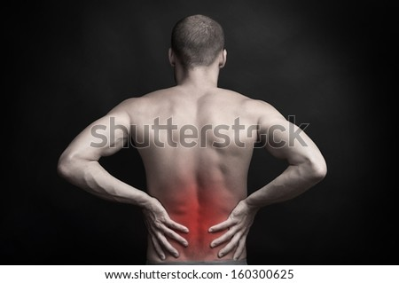 strong muscular man holding his aching back with hands - spine ache concept