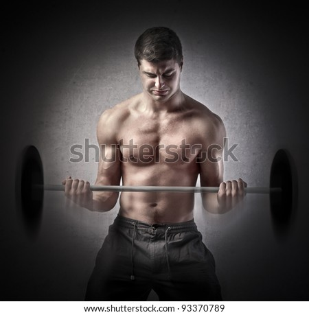 Strong muscular man lifting weights