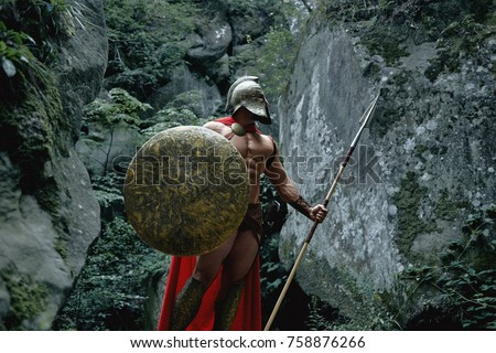 Strong muscular medieval warrior in battledress posing with a shield and spear.