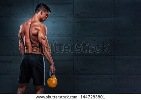 Strong Muscular Men Exercise With Kettlebell