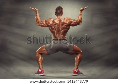 Strong Muscular Men Flexing Muscles from the Back. He is showing back muscles development