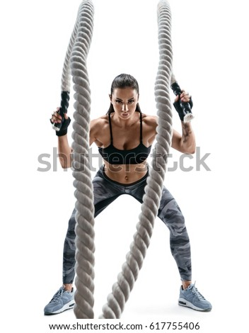 Stock Photo Strong muscular woman working out with ropes. Photo of attractive woman in sportswear isolated on white background. Strength and motivation.
