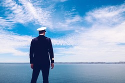Strong posture of a captain looking at the sea and faraway land on the horizon. Navy/Cruise ship concept. Outdoor shot.