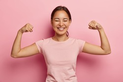 Strong powerful Asian woman with dark combed hair, toothy smile, raises arms and shows biceps, has piercing in ear, wears casual rosy t shirt, models against pink background. Look at my muscles!
