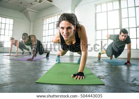 Strong powerful intense fit female leader of athletic fitness team exercising one arm push ups #504443035