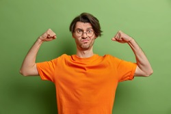Strong powerful man raises arms and shows muscles after training in gym has aim to be healthy and fit smirks face wears round spectacles and casual orange t shirt isolated over green background