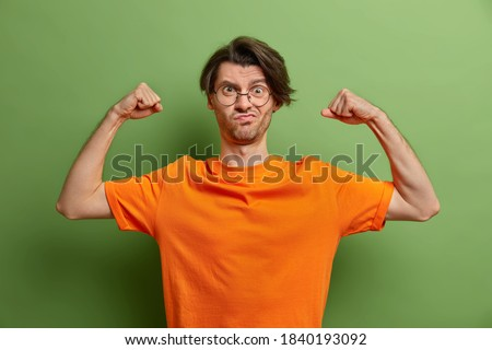 Strong powerful man raises arms and shows muscles after training in gym has aim to be healthy and fit smirks face wears round spectacles and casual orange t shirt isolated over green background ストックフォト ©
