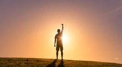 Strong powerful young determined man with fist up to the sky. Never giving up, and physical and inner strength.